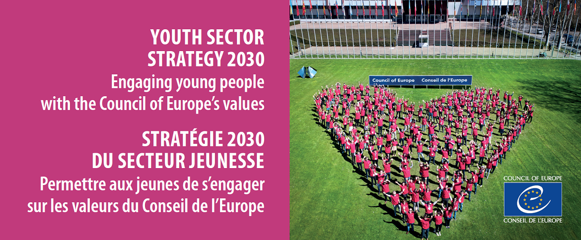 "Banner ""Youth sector strategy 2020, engaging young people with the Council of Europe's values"" and image of young people in the shape of a heart on the Council of Europe front lawn"