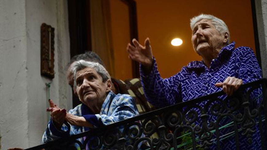 Elderly women stand on a balcony in Pamplona, Spain on 15 March 2020.