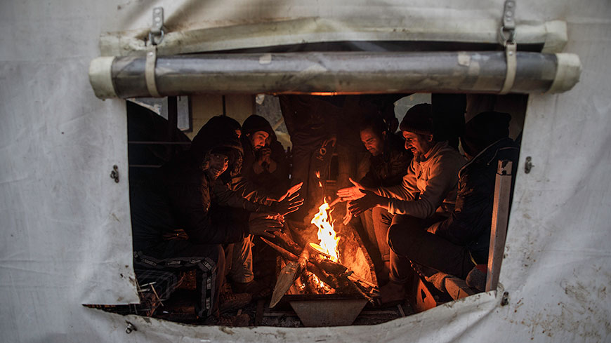 Migrants warm themselves by the fire set in one of the tents in Vucjak camp, 25 November 2019, © Damir Sagolj / Council of Europe Commissioner for Human Rights
