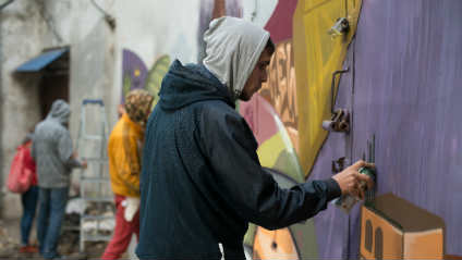3 youth working on graffiti