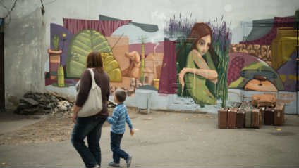 woman holding hands with young boy passing by a graffiti of a woman