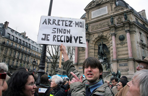 A man protests the law, which prohibits to provide aid to illegal immigrants - 8 April 2009 at Place St. Michel in Paris, France. The poster says 'Arrest me, otherwise I do it again' Olga Besnard / Shutterstock.com